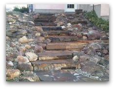 This newly completed project is waiting for shrubs to add some colour. These natural stone slab steps and rock garden, replaced a steep, slippery, and often  muddy hill. via dream-yard.com