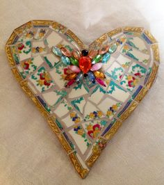 Mosaic heart, 6¾ x 5½. Handmade heart from concrete and free-hand shaped. Embellished with vintage tiles and a beautiful vintage butterfly brooch. A wire for hanging is embedded into the concrete on the back.