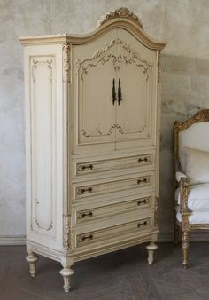 French white armoire with soft gold detailing. Pediment, decorative hardware, and turned legs.
