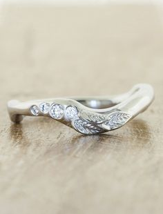 The wave-like contours of the Trisrepresent eternal love, despite all of its unexpected twists and turns. Pairs beautifully with theAurora engagement ring. H