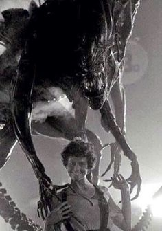 "Behind the scenes on ""Aliens"", Sigourney Weaver posing with the Alien."