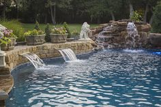 Natural rock fountain, waterfall, and two smooth waterfalls flowing into this custom freeform swimming pool in Oklahoma City, OK by Red Valley Landscape & Construction.