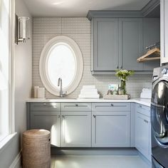 Blue-gray laundry room cabinet paint color. Blue-gray laundry room cabinet with quartz countertop. Quartz makes one of the best laundry room countertop choices for its durability. #laundryroom Elizabeth Metcalfe