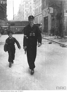 Two Polish soldiers, father and his son, walking down the street during the Warsaw Uprising, Warecka Street, Warsaw, Poland, August 1944