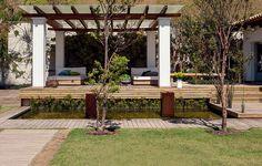 Em primeiro plano, duas cerejeiras-do-rio-grande. Na área do spa, chaises de casal desenhadas pela decoradora Rita Diniz. Rente ao muro, pleomeles. Projeto executado pela SHM Arquitetura.