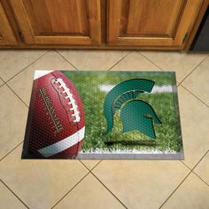Michigan State Scraper Mat 19x30 - Ball - Scraper Mats by Sports Licensing Solutions are great for showing off your team pride in high traffic areas! Scraper Mats have nibs that scrape shoes clean of dirt, debris, and moisture so that your home stays clean. The debris is then trapped below the walking surface. Clean up is a breeze, just use a hose. Rubber construction ensures durability and mat features a high resolution image that won't fade! Textured backing keeps mat in place.FANMATS…