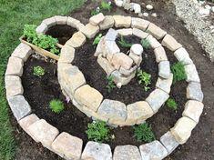 Kräuterspirale aus Naturstein mit Gartenteich unten