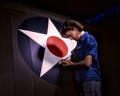 Restored Vintage World War II Color photo of a woman working in the Vultee Aircraft Factory in Nashville, TN, painting an Army Air Force Insignia.