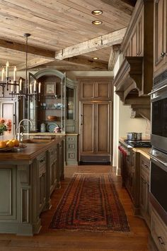 An L-shaped rustic country kitchen with a red floral-patterned rug between the main cooking area and the kitchen island. The island, in a muted green-gray, matches the china cabinet on the far wall, which displays varied pieces of pottery. The exposed beam ceiling really adds to the rustic charm of this country kitchen.