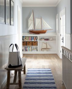 HALLWAY - shelves at end of hall with books & Nautical sailboats Bear & Hill Interiors: http://www.bearhillinteriors.com/Brighton/index.html