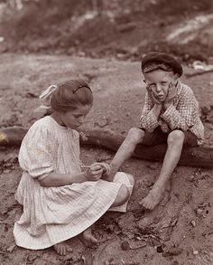 1910...A young girl removing splinter from toe of a young boy