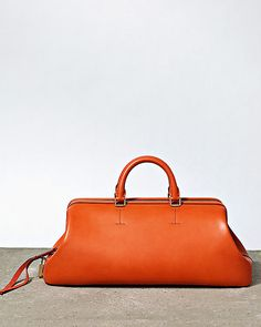 Celine reinterprets the doctor's bag. Celine'sWinter bag is a a stripped down modern take of the doctor's bag with a body made of bonded shiny calf material. Orange Handbag, Orange Purse, My Bags, Purses And Bags, How To Have Style, Celine Bag, Frame Bag, Oui Oui, Cute Purses