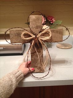 Cross. Used old wood from a barn, old, rusty barbed wire, an old barn star and raffia. I made this for my sister in law's bday.