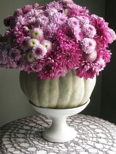 Select an unconventional pumpkin shade like this grayish-green hue and fill with a simple arrangement of purple mums (shoot for any color but autumn tones!). Add height to your arrangement by placing it on a pedestal.