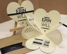 Laser cut engagement invitation folds from a clover shape into a heart and fastened with a ribbon sticker combo.