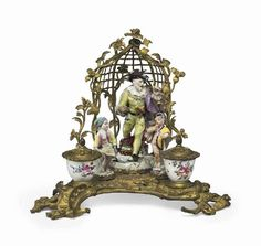 A FRENCH ORMOLU-MOUNTED MEISSEN AND MENNECY PORCELAIN ENCRIER THE PORCELAIN LARGELY CIRCA 1765, THE MOUNTS 19TH CENTURY The central figure as a potion seller from the commedia dell'arte, flanked by two putti disguised as a pastry seller and a snuff-taker, in a trellis arbor, the inkwell and sander painted with floral sprays, raised on a naturalistic base 9½ in. (24 cm.) high (4)