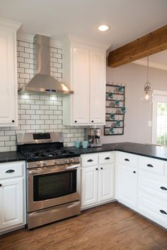 Fixer Upper hosts Chip and Joanna Gaines renovated the homeowners' kitchen and added a new stainless steel range and vent hood surrounded by a beveled subway tile backsplash. Crisp white cabinetry and black marble countertops complete the stylish look.