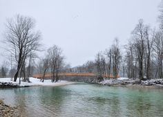 Arching wooden footbridge connects Slovenian village to the nearby lakes and mountains.