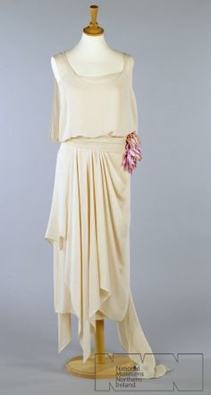 1920's Evening dress of pale pink silk crepe, sleeveless with low back joined at waist. An under-dress has ribbon straps and hooked opening left side seam. Overdress has bodice draped to waist with open side seam, skirt gathered and draped to handkerchief point at front right hip with long floating panel from backt left hip which extends the train to the floor. Via National Museums Northern Ireland.