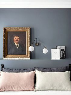 gray blue bedroom with modern globe light fixture and vintage portrait painting on a shelf above the bed / sfgirlbybay
