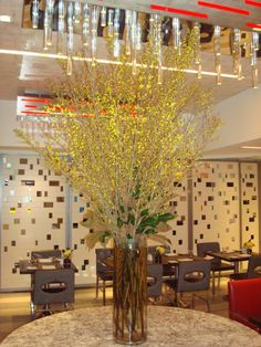 A tall cylinder featuring yellow forsythia branches.  To view our entire selection please visit us at www.starflor.com #flowers #events #eventdecor