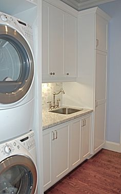 washer dryer stacked with curtain, cupboards, storage