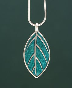 Hues of green and teal set the backdrop for the tree of life and leaf design in this pendant necklace.
