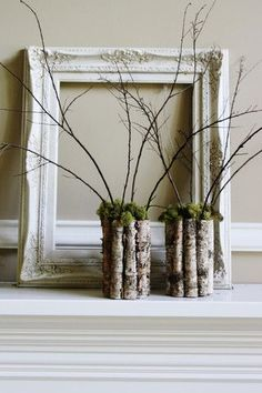 Decor by Joanna Gaines of Magnolia Farm. Empty frame and vases made of sticks and moss.