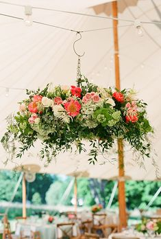 A tented reception becomes a garden-inspired bash with the help of these lush floral chandeliers that are filled with bright pink peonies, hydrangea, and greenery | Brides.com