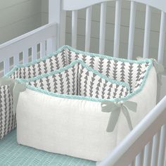 "Crib Bumper in Gray and Aqua Arrow Stripe by Carousel Designs.  Our four-sided crib bumpers are produced in one continuous piece and fit standard cribs (using mattresses measuring approximately 28"" x 52"") and meet regulation standards with approximately 12"" long ties and 2-3"" thick batting, so that you can rest easy. Our crib bumper batting is made from recyclable hypoallergenic polyester fiberfill."