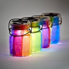 rainbow wedding decor LED candles inside crepe paper covered / lined jars.