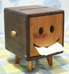 Toilet paper holder, BUT could be modified to hold a square kleenex box, turning mouth upside down to a frown. No roller.