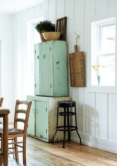 Rustic farmhouse kitchen with interior design by Leanne Ford. Two vintage country cabinets are stacked vertically, and a rustic wood bread board hangs on a hook from the board and batten wall.