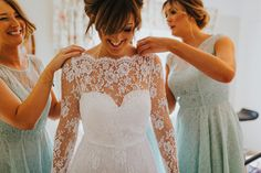 Bridesmaids lending a helping hand with the finishing touches. Photo by Benjamin Stuart Photography #weddingphotography #bride #bridesmaids #weddingdress #lacedress #vintagedress #gettingmarried