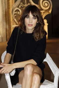 Alexa Chung at Caroline Sieber in a black jumper, a tweed skirt and a velvet Chanel bag.