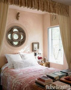 The faded pink walls and cream-colored curtains in designer Penelope Bianchi's bedroom continue the overall Mediterranean-style seen throughout her Santa Barbara, California home. With her love of antique fabrics, an 18th-century toile — purchased off of eBay for $140 — is a favorite find that she uses on her bed.   - HouseBeautiful.com