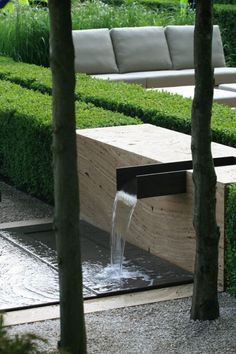 Hedges in this tableau are precisely clipped to the shape of the fountain, composed of a metal spout in stone that empties into a shallow basin set in stone and crushed pebbles.