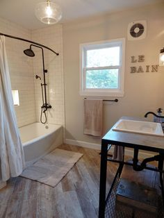 Complete bathroom remodel in the modern farmhouse style with a custom welded iron vanity (with metal found on the property), heated floors, distressed wood tile, and subway tile, and concrete countertop