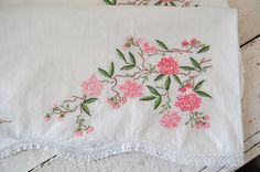 What a beautiful pair of pillowcases! Embroidered pretty pink cherry blossom branches ramble along the bottom of these cases. A very pretty & great