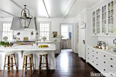 "Kitchen walls are sheathed in subway tiles ""like the French bakeries I love,"" designer and owner Jeannette Whitson says of her Nashville house. ""And I designed long, shallow drawers like those in old English servants' quarters."" The nine-and-a-half-foot island is topped with Calacatta marble and has a sink fitted with a Waterstone Gantry faucet. A custom steel hood is paired with a Lacanche range."