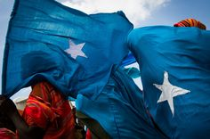 Women carry Somali flags in Mogadishu, Somalia, as they wait for the arrival of the Prime Minister