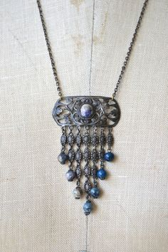 Vintage 1930s gunmetal silver filigree pendant necklace with marbelized lapis colored center stone above dangling silver links punctuated with repeated blue glass beads. ------ M E A S U R E M E N T S -------  21.5 length 2.75 drop maker/markings: n/a condition: excellent  ➸ to shop more vintage jewelry http://www.etsy.com/shop/DearGolden?section_id=7337115  ✩ visit the shop ✩ http://www.DearGolden.etsy.com  _____________________  ➸ instagram | dea...