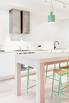This all white kitchen has the perfect touch of minty green color! Minimal design elements combine w/ a large table & green stools, in this modern kitchen design.