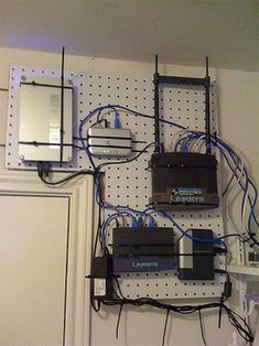 Using peg boards and zip ties to organize your routers. If you had somewhere inconspicuous to put them on the wall like this (under the desk?), sweet.