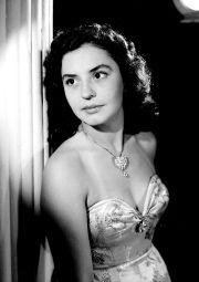 Silvia Derbez, junto a una columna, usa vestido de hombros descubiertos, retrato