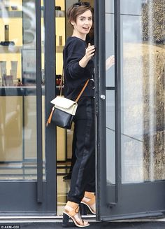 Lily Collins bares her taut midriff in a plunging striped tank top and cropped jeans as she goes on solo shopping spree