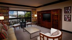 Living room with a sofa and 3 chairs opposite a large wood media cabinet housing a flat-screen TV and adjacent to a balcony Polynesian Suite Florida Resorts, Disney World Resorts, Walt Disney World, Polynesian Village Resort, Disney Planning, Media Cabinet, Patio, Balcony, Living Room