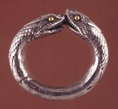 1st Century, Roman. Silver finger-ring ending in snakes' heads. The scales are hatched, the eyes are made of gold pellets.