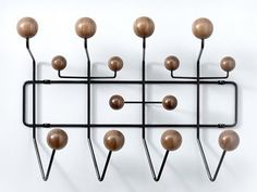 With their Hang-It-All, Charles and Ray Eames made the everyday coat rack inventive and fun. Their whimsical original design features a white frame and multicolored hooks.  The Herman Miller Select 2010 Edition reinterprets this classic with solid walnut hooks against a black frame. Want!