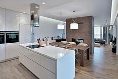 Kuchyň s jídelním stolem a obývacím pokojem tvoří jednu místnost, kterou rozděluje pouze krb s oboustrannou krbovou vložkou obložený keramickým obkladem zemité barvy